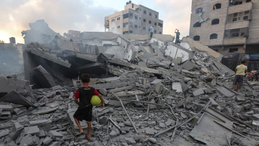 A boy looks at the rubble of a building in Gaza City after an Israeli airstrike on Aug. 9.