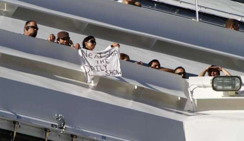 A passenger aboard the Carnival Splendor waves a T-shirt message as the cruise ship is tied up in San Diego Harbor in 2010.