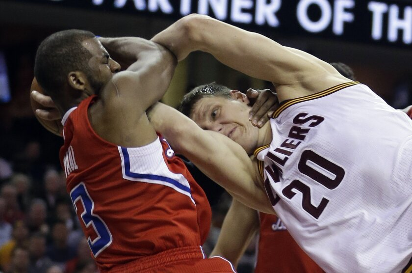 Los Angeles Clippers' Chris Paul (3) is called for a flagrant foul against Cleveland Cavaliers Timofey Mozgov (20) during the second quarter of an NBA basketball game Thursday, Feb. 5, 2015, in Cleveland. (AP Photo/Tony Dejak)