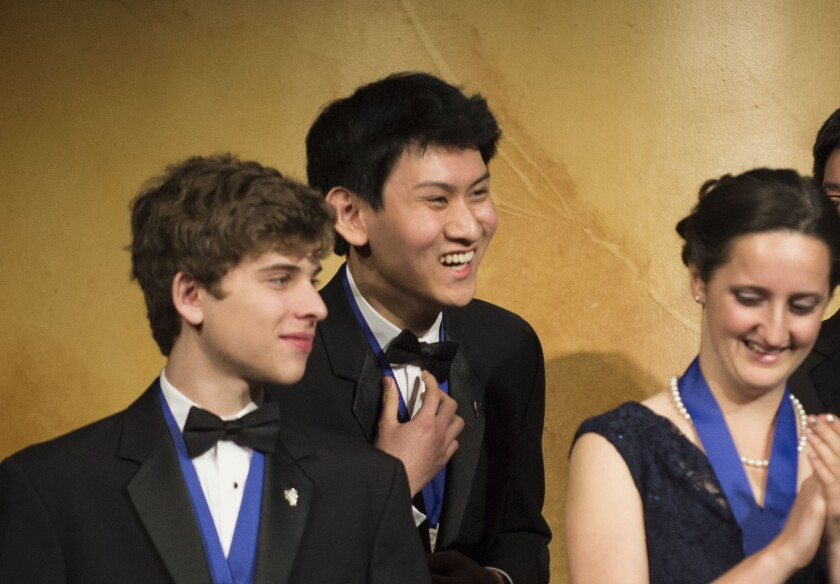 Eric S. Chen reacts to winning first prize at the Intel Science Talent Search. With him are finalists Alec Vadim Arshavsky and Kathy Camenzind.