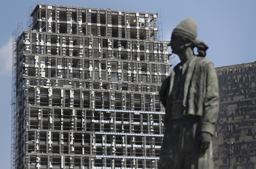A statue representing the Lebanese expatriate is seen in front of a building that was damaged by an explosion that hit the seaport of Beirut, Lebanon, Wednesday, Aug. 5, 2020. Residents of Beirut confronted a scene of utter devastation on Wednesday, a day after a massive explosion at the port rippled across the Lebanese capital, killing at least 100 people, wounding thousands and leaving entire city blocks flooded with glass and rubble. (AP Photo/Hussein Malla)