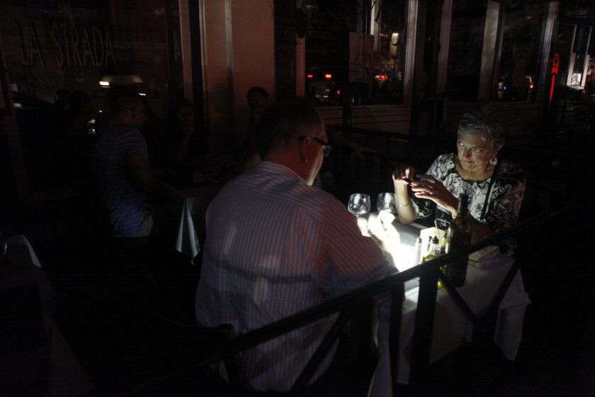 Downtown was dark as the sun set but many people continued to enjoy themselves downtown in the Gaslamp quarter.  At the Restaurant La Strada, diners used cell phones to see the menu and sign the bills on their credit card. Here Ellen and David Livingston read the bill at La Strada with their cellp