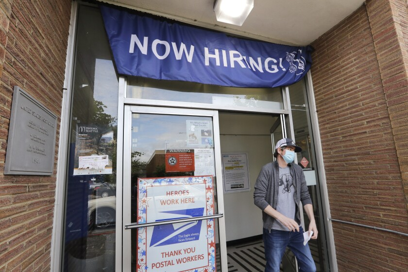 FILE - In this June 4, 2020, file photo, a customer walks out of a U.S. Post Office branch and under a banner advertising a job opening, in Seattle. Unemployment remains painfully high in the U.S. even as economic activity is slowly picking up. That reality will be on display Thursday, July 16, 2020, when the U.S. government releases data on the number of laid off workers seeking unemployment benefits the week prior and retail sales in June. (AP Photo/Elaine Thompson, File)