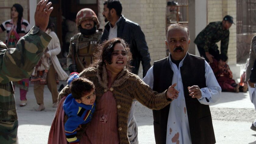 A man helps an injured woman and a child following an attack on a church in Quetta, Pakistan, Sunday