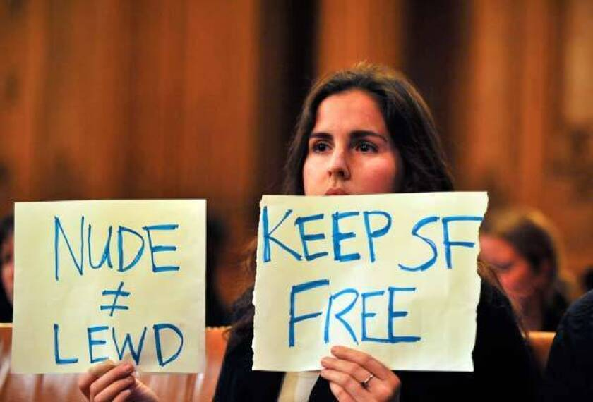 Tailor Whitfield holds up a sign during a Board of Supervisors meeting in San Francisco's City Hall.