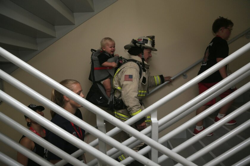 Rancho Sante Fe Deputy Chief Fred Cox carried one year old Jack Duncan on his third trip up during the San Diego Memorial Climb Fundraiser to honor those killed on 9/11. Cox was giving Jack's father, Troy, not pictured, a break who had climbed with his son earlier.