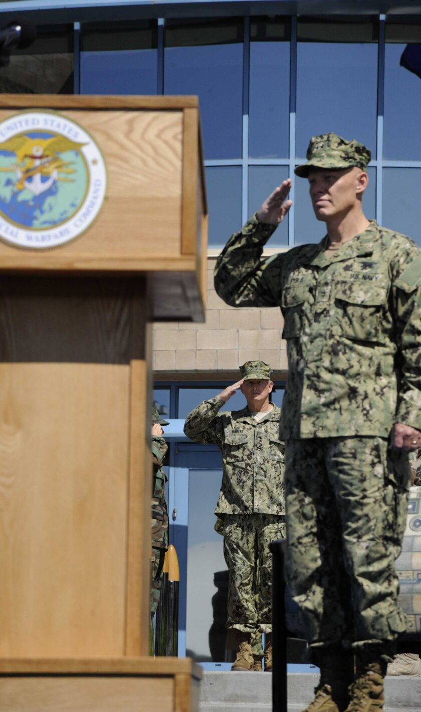 Rear Adm. Sean Pybus, right, salutes at the Naval Special Warfare Command change-of-command ceremony. Outgoing commander Rear Adm. Edward Winters is on the left.