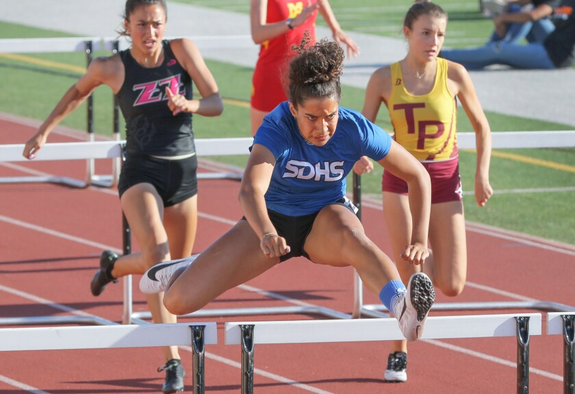 Sonia Redon, of San Diego High School, wins the hurdles.