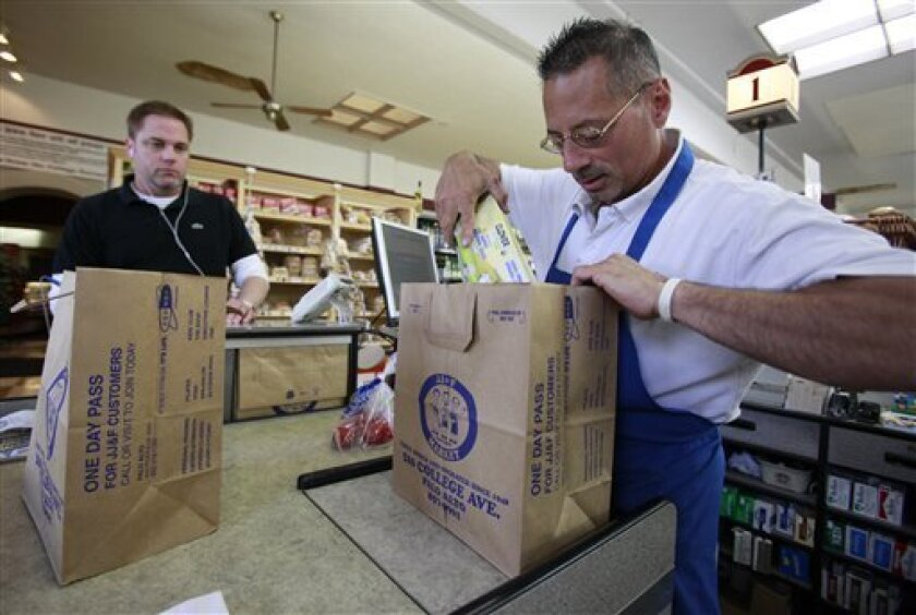 Grocery store clerk Mike Saladino places a customer's purchased items in a paper bag in Palo Alto, Calif., Wednesday, June 2, 2010. It could soon cost California shoppers at the checkout if they forget to bring their own bag to the grocery store under what would be the nation's first statewide plastic bag ban. The California Assembly on Wednesday passed legislation that would prohibit grocery stores, pharmacies, liquor stores and convenience stores from giving out free plastic and paper bags. If signed into law, California would be the first state to impose such a ban. (AP Photo/Paul Sakuma)
