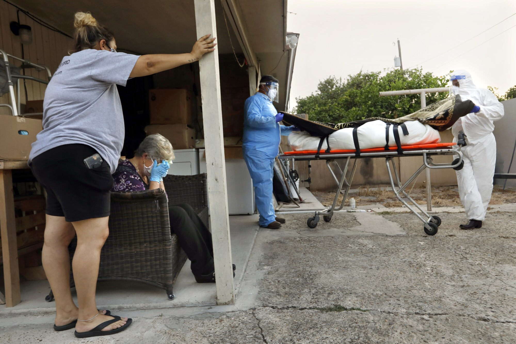 Maura Ramirez, standing, watches as Juan Lopez and Elizandro Flores remove the body of her mother from her home.