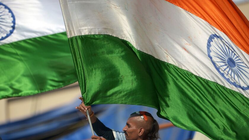 An Indian cricket supporter waves the Indian flag at a rally in Kolkata on March 18, 2016.