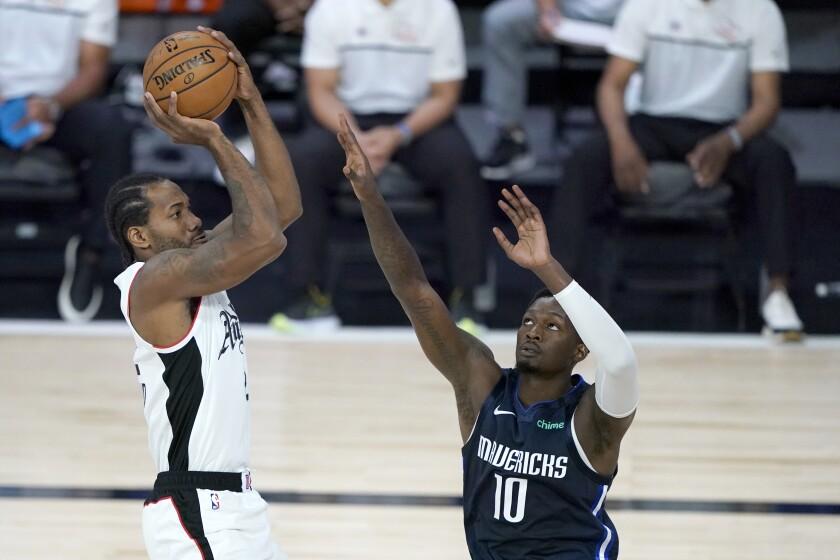 Clippers forward Kawhi Leonard pulls up for a mid-range shot against Mavericks forward Dorian Finney-Smith.