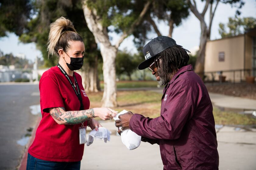 An outreach worker offers a hygiene kit to an unidentified unsheltered man in San Diego.