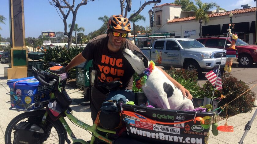 Mike Minnick and Bixby the dog on a travel break in Encinitas on Friday. They've traveled by bike ne