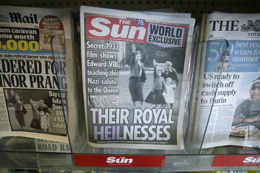 Vista de portadas de periódicos que publican la imagen de la reina Isabel II de Inglaterra, de joven, haciendo el saludo nazi, en una tienda de Londres, el 18 de julio de 2015.El Palacio de Buckingham mostró su malestar por la publicación en un tabloide británico de una fotografía de una joven Isabel II realizando un saludo nazi con su familia en 1933, el año en que Adolf Hitler llegó al poder en Alemania. (Foto AP/Tim Ireland)
