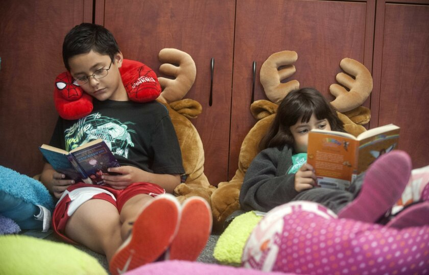 Fernando Nater, left, and his sister, Isabella Nater, spend some quiet time at the Learning Center in Vista to read during a summer reading program. Fernando is the program's top reader with 5.2 million words -- and counting.