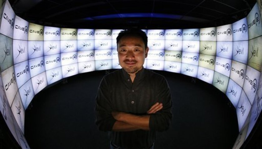 In this photo taken Thursday, Jan. 24, 2013, in Chicago, University of Illinois-Chicago computer scientist Jason Leigh, co-inventor of the CAVE2 virtual reality system, stands in the CAVE2's doorway where the system's 72 stereoscopic liquid crystal display panels  encircles the viewer 320 degrees