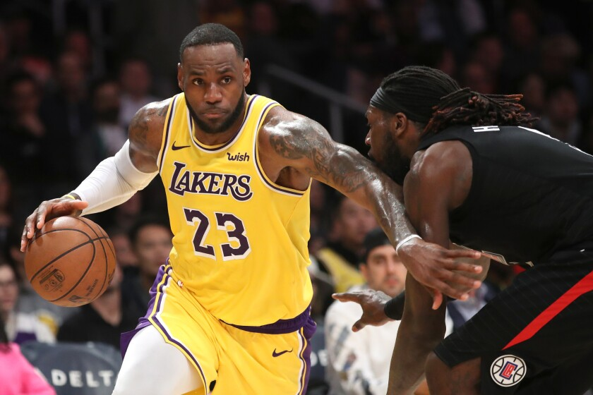Lakers' LeBron James dribbles past Clippers' Montrezl Harrell at Staples Center.