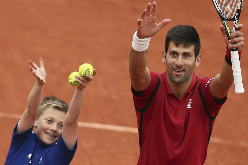 Serbia's Novak Djokovic celebrates with a ball boy after winning the quarterfinal match of the French Open tennis tournament against Tomas Berdych of the Czech Republic in three sets, 6-3, 7-5, 6-3, at the Roland Garros stadium in Paris, France, Thursday, June 2, 2016. (AP Photo/David Vincent)