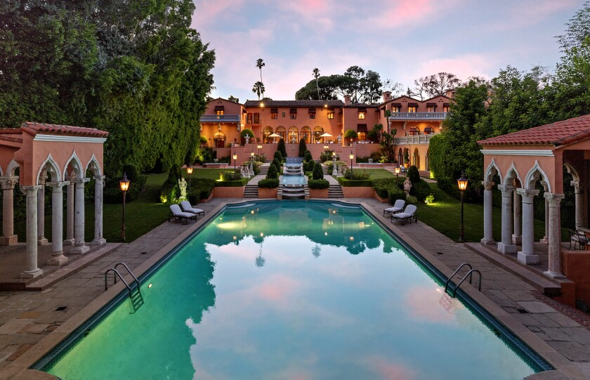 A mansion with a pool in the foreground.