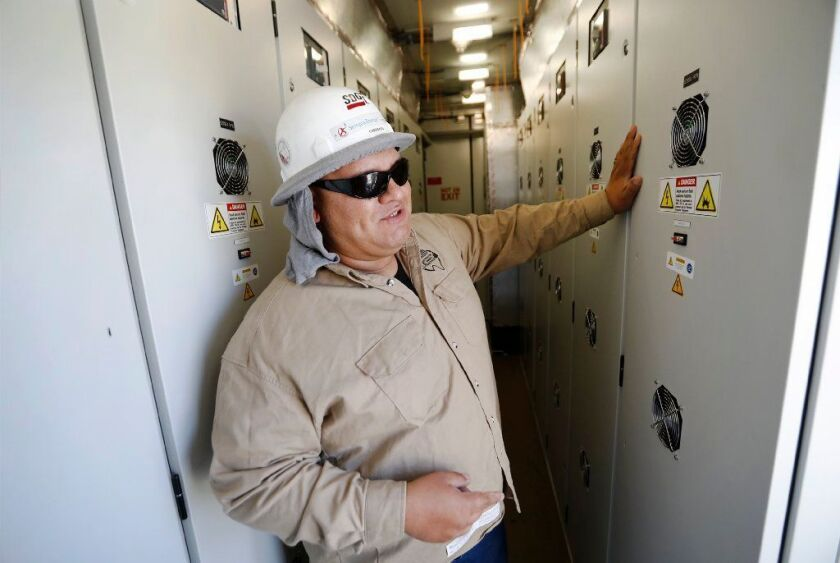José Cardenas, an engineer with SDG&E, shows the interior of one of several shipping containers packed with lithium-ion batteries at the utility's microgrid in Borrego Springs.