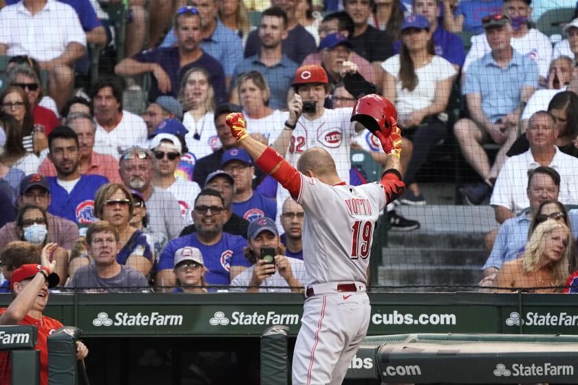 Joey Votto festeja a su regreso al dugout después de conectar un cuadrangular por los Rojos de Cincinnati en el tercer episodio del duelo ante los Cachorros de Chicago, el martes 27 de julio de 2021, en Chicago. (AP Foto/David Banks)