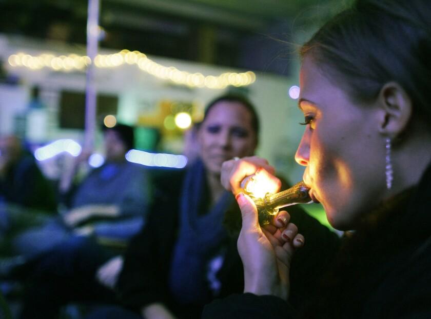 En esta fotografía de archivo del 31 de diciembre de 2012, Rachel Schaefer de Denver fuma marihuana en la inauguración del Club 64, un club social enfocado en la hierba, donde se llevó a cabo una fiesta por el Año Nuevo, en Denver. En esta ciudad se realiza una campaña para preguntarle a los electores en las boletas de noviembre si se debe permitir el consumo de marihuana en bares y otros sitios a los que sólo pueden asistir personas mayores de 21 años.