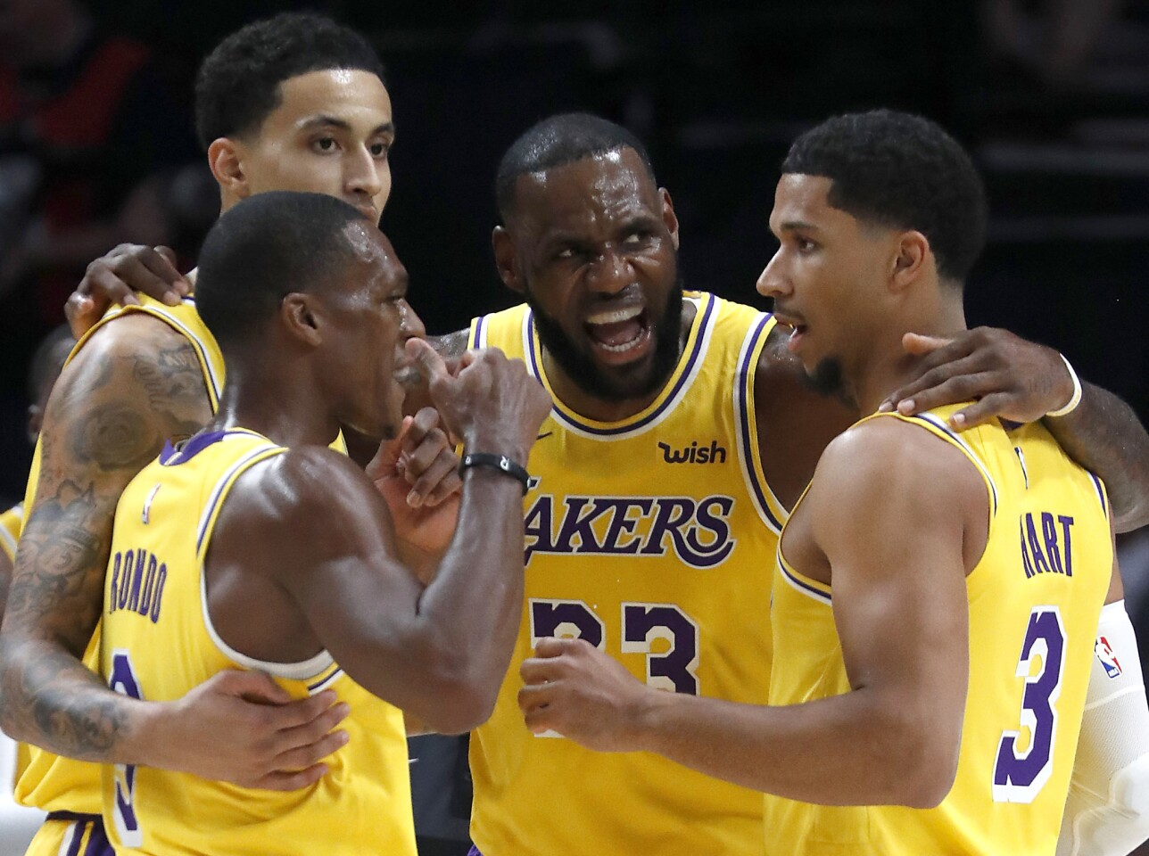 Lakers forward LeBron James huddles with his teammates during the season opener against the Trail Blazers.