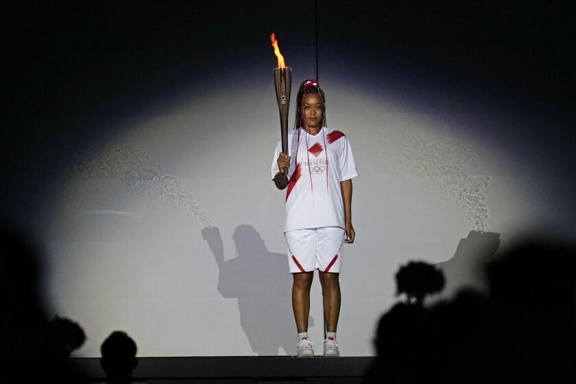 La tenista Naomi Osaka sostiene la antorcha durante la ceremonia de inauguración de los Juegos Olímpicos,