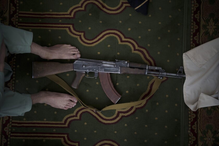 A Taliban fighter lays his AK-47 rifle down during Friday prayers at a Mosque in Kabul, Afghanistan, Friday, Sept. 10, 2021. (AP Photo/Felipe Dana)