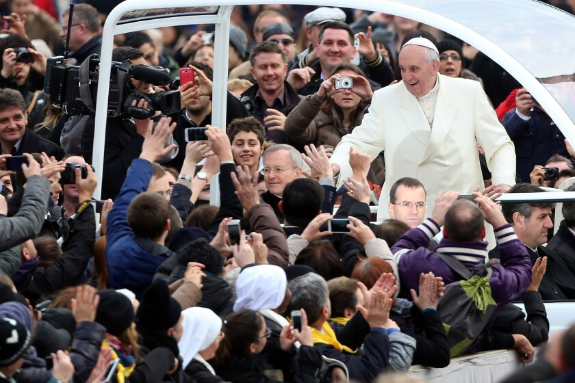 Pope Francis waves to the crowds as he arrives in St. Peter's Square in the Vatican City for his weekly audience.