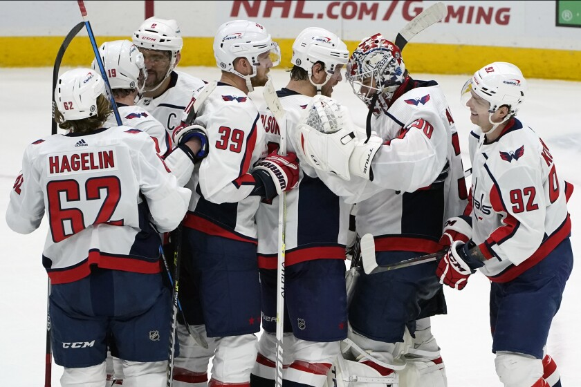 Washington Capitals center Evgeny Kuznetsov, (92) and teammates congratulate goaltender Ilya Samsonov (30) after the Capitals defeated the New York Islanders 1-0 in a shootout in an NHL hockey game Thursday, April 22, 2021, in Uniondale, N.Y. Kuznetsov scored in the shootout. (AP Photo/Kathy Willens)