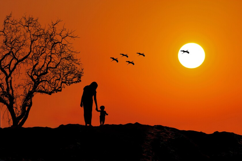 Adult and child walk at sunset