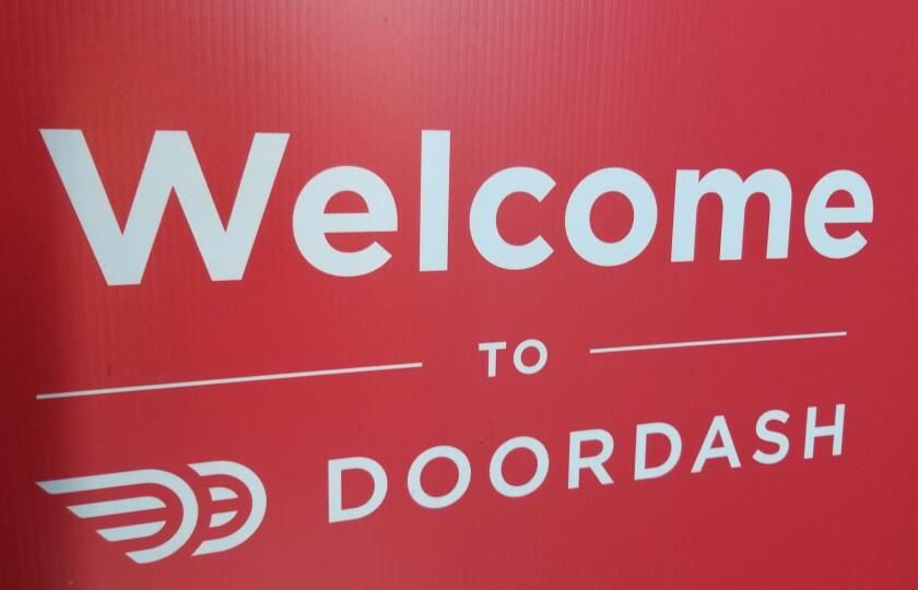 """A red sign that says """"Welcome to DoorDash."""""""