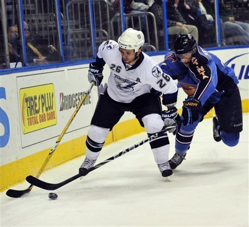 Atlanta Thrashers center Rich Peverley, right, fights for the puck against Tampa Bay Lightning right wing Martin St. Louis (26) during the first period of an NHL hockey game at Philips Arena, Tuesday, Feb. 2, 2010, in Atlanta. (AP Photo/Gregory Smith)