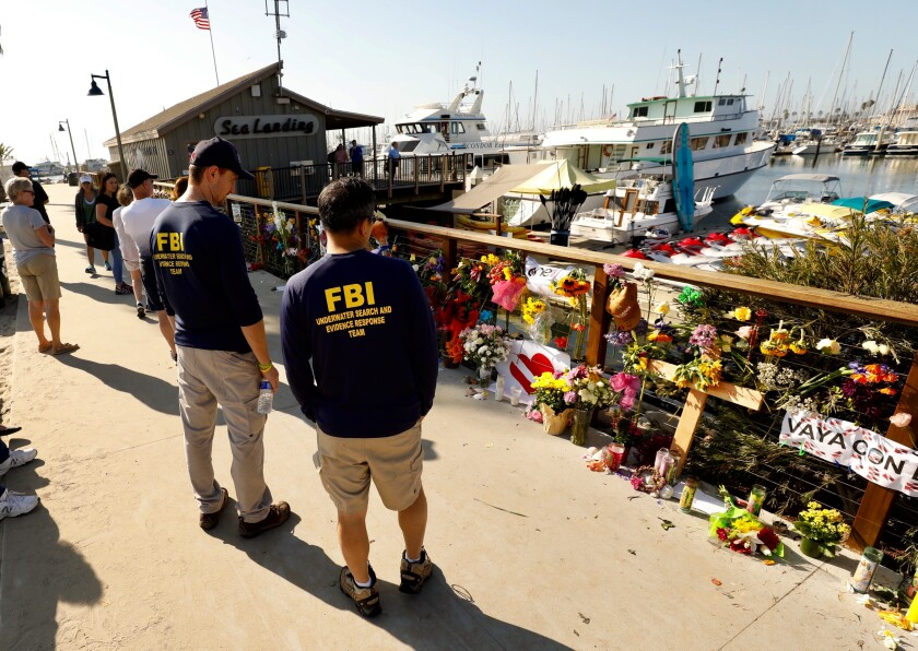 Members of an FBI dive team look at a growing memorial to the victims of the Labor Day fire aboard the Conception.