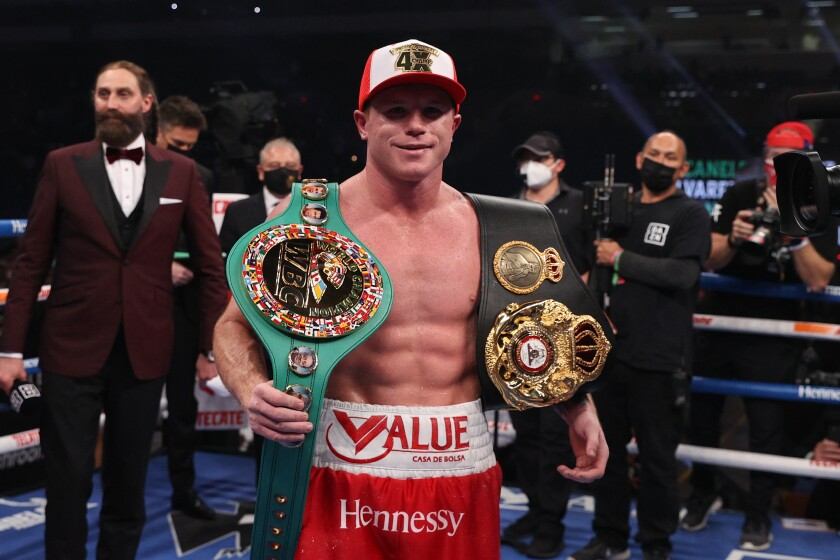 Canelo Álvarez poses with his belts.