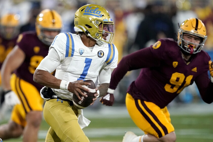 UCLA quarterback Dorian Thompson-Robinson is chased by Arizona State defensive end Michael Matus.