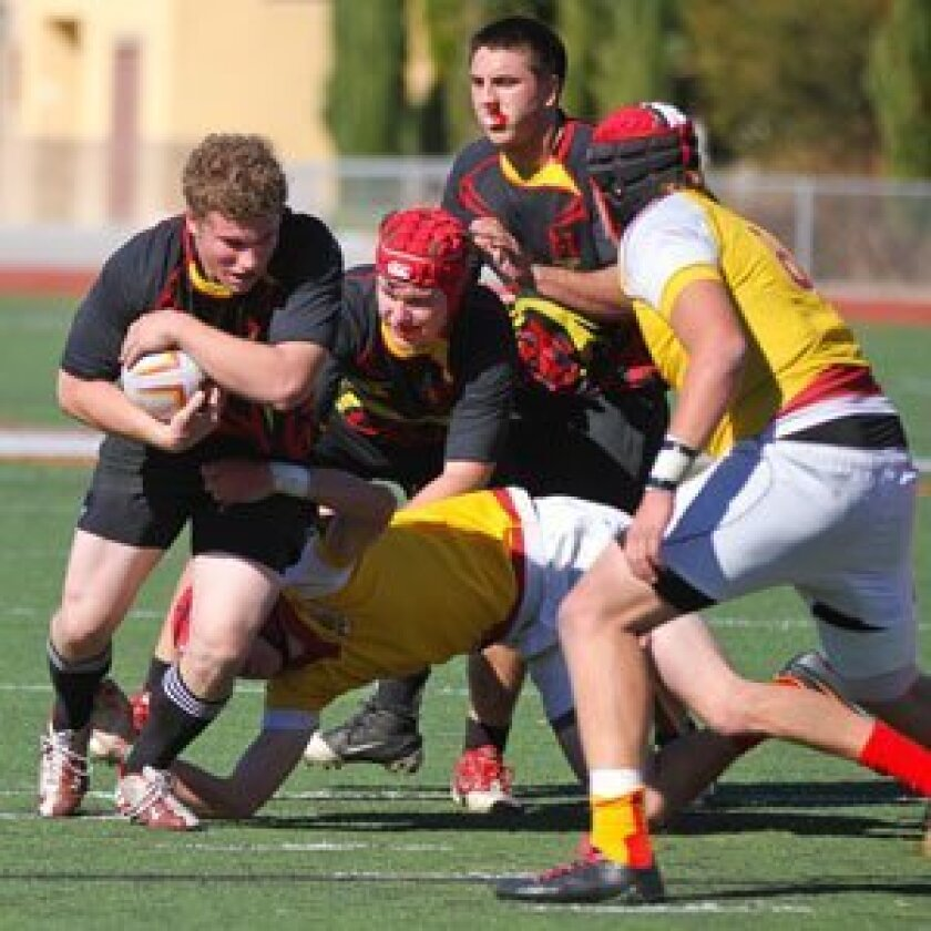 Torrey Pines Senior Miles Ahles breaks a Cathedral tackle, while teammates AJ Talman (middle with cap) and Grant McGahey run up in support. Don's All-American Drew Gaffney (#8, foreground) gets ready for the take-down. Photo/Susie Talman