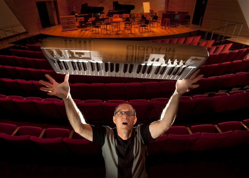 Composer Rand Steiger with one of his keyboards inside the concert hall at the Conrad Prebys Music Center on the UCSD campus. As chairman of the university's music department from 2006 until this year, Steiger oversaw the creation of the center.
