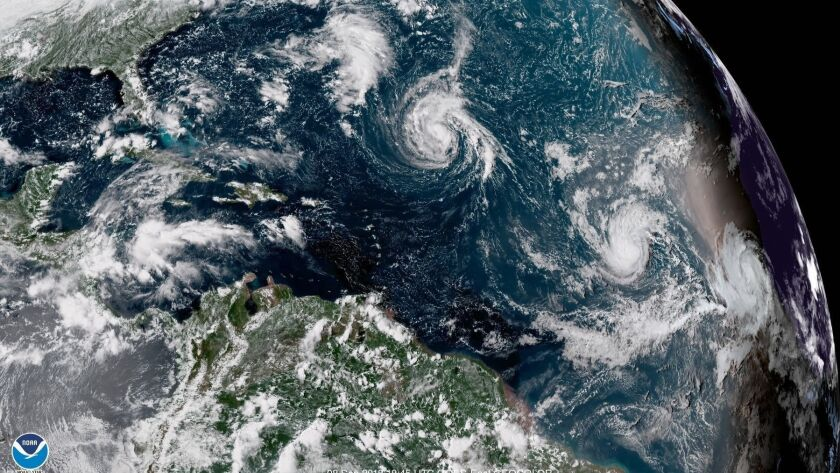 This enhanced satellite image made available by NOAA shows Tropical Storm Florence, center, in the A