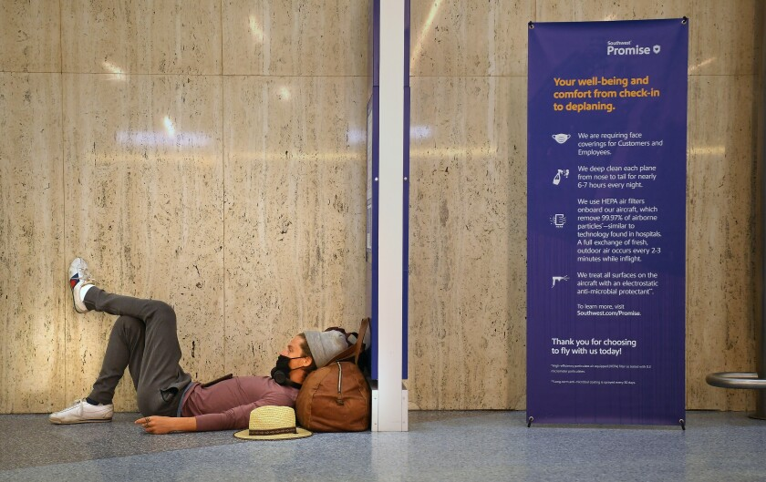 A traveler sleeps at LAX next to a sign describing the airport's COVID cleaning protocols.