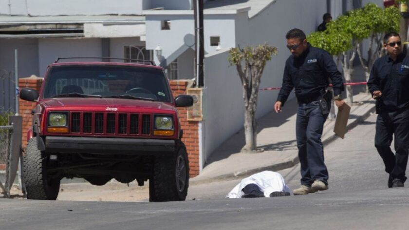 State homicide investigators work at the scene of the murder of Tijuana Municipal Police Officer Jose Luis Nuñez Lopez, 27, where he was gunned down while leaving his house on Aug. 1 in the Jardines del Rubi.