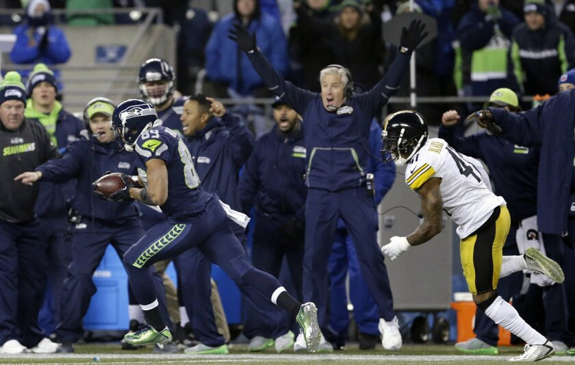 Seattle Seahawks head coach Pete Carroll, center, cheers as Doug Baldwin, left, races past toward a touchdown, followed by Pittsburgh Steelers' Antwon Blake late in the second half of an NFL football game, Sunday, Nov. 29, 2015, in Seattle. (AP Photo/John Froschauer)
