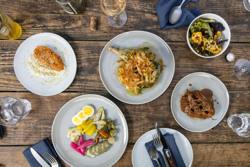 Bar Avalon's offerings (clockwise from top left): Carrot halwa; roast chicken with root vegetables and carrot-top pesto; cauliflower served with anchovy and calabrian chiles; piri piri blue prawns with preserved lemon; and the pickle plate.
