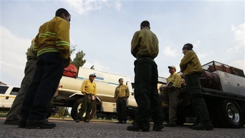 Firefighters from Wildland Defense Systems Inc., debrief after a day on the Waldo Canyon wildfire west of Colorado Springs, Colo., Friday, June 29, 2012.  Wildland Defense Systems Inc., is a private company that provides firefighters for insurance company Chubb Personal Insurance, one of a handful
