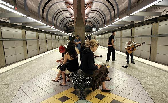 A man with his guitar serenades passengers waiting for a subway train at the Hollywood-Highland station in Los Angeles.