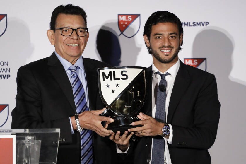 Former Dodgers pitcher Fernando Valenzuela poses with LAFC's Carlos Vela with Major League Soccer's Most Valuable Player trophy.