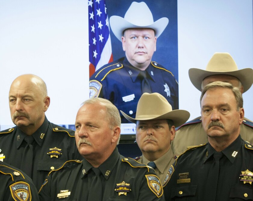 FILE - In this Saturday, Aug. 29, 2015 file photo, law enforcement officers attend a news conference in Houston on the shooting death of Harris County Sheriff's Deputy Darren Goforth, pictured in the background. In May 2016, Louisiana is poised to become the first state in the nation to expand its