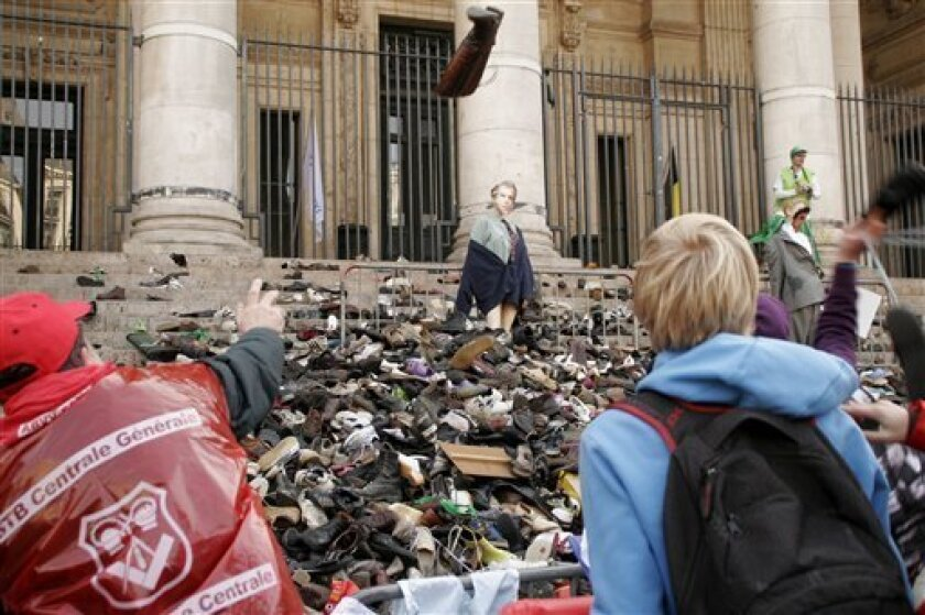Workers in the non-profit sector, throw shoes towards a dummy of Belgian Prime minister Yves Leterme, center top, on the steps of the stock exchange building in Brussels, during a protest, Tuesday, March 29, 2011. The non-profit sector, numbering some 450,000 people, complains about the absence of a new working agreement, partly the result of Belgium lacking a fully fledged government. (AP Photo/Elisa Day)